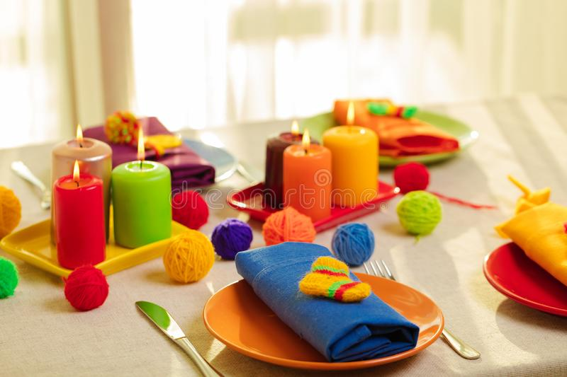 Multicolored plates and linen napkins with knitted decor. Table stock photo