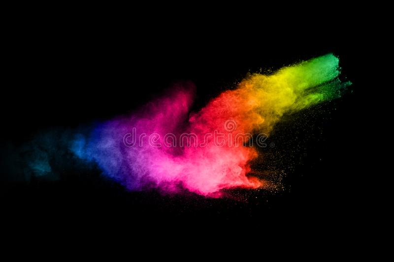 Multicolored powder explosion on black background.Color dust splash cloud on dark background.Launched colorful particles stock images
