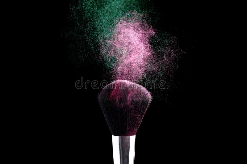 Multicolored powder is scattered around the makeup brush, frozen movement of the powder particles flight. copy space royalty free stock photography