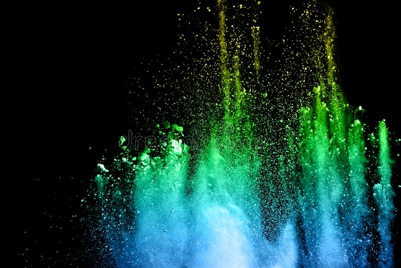 Multicolored powder splash on black background. Colorful dust splattered on dark background stock image