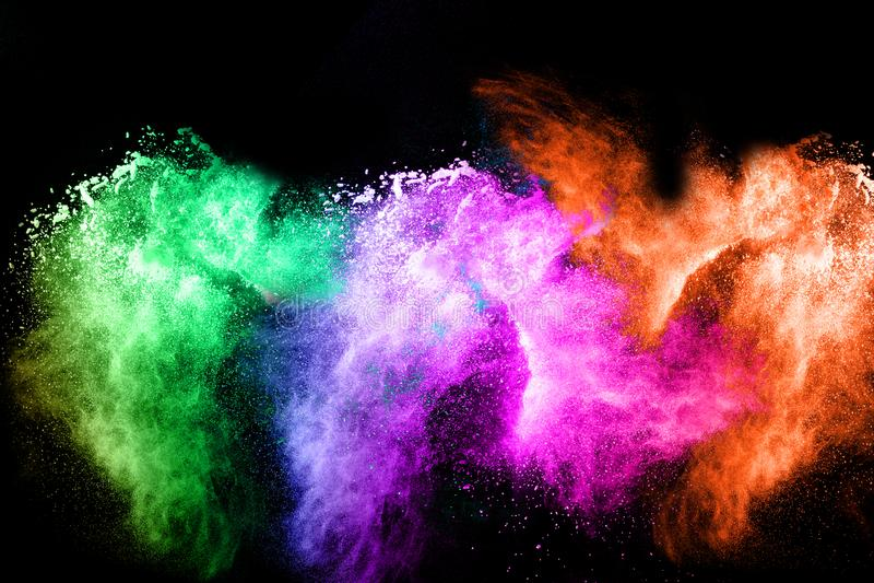 Multicolored powder splash on black background. Colorful dust splattered on dark background royalty free stock photo