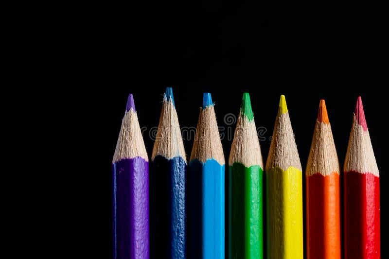 Multicolored rainbow pencils. Coloured pencils isolated on black background close up. Top view. Macro Photography. Pencils Wallpap stock photos