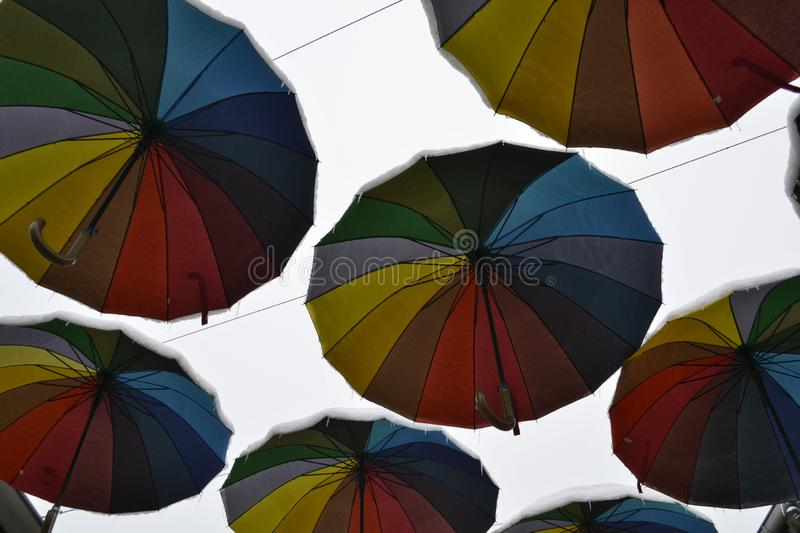 Multicolored rainbow umbrellas in the sky covered with snow stock photography
