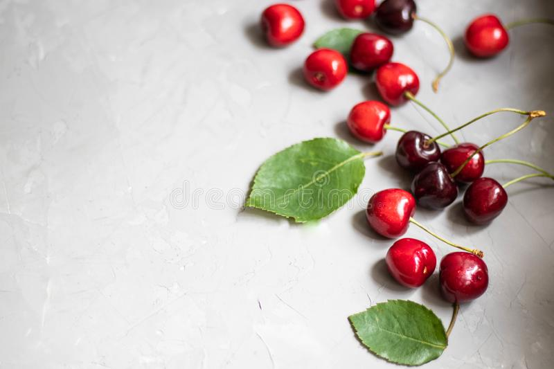 Multicolored, red and maroon large sweet cherries lie on a gray, stone background, decorated under concrete. royalty free stock photography