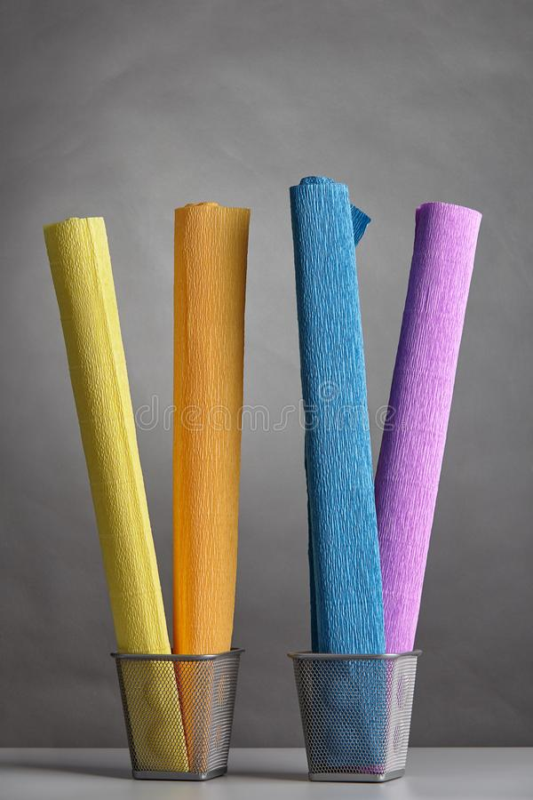 Multicolored rolls of wrinkled crepe paper stand upright in bask stock images
