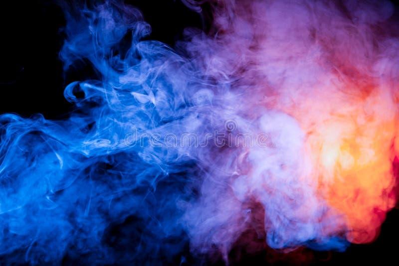 Multicolored rook zoals kosmisch stof van blauwe, rode, magenta en vurige sinaasappel op een zwarte is verpakt in ringen stock afbeeldingen