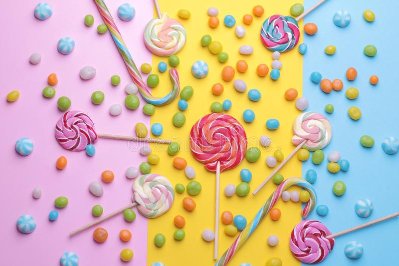Multicolored round candy and colored lollipops on colored bright backgrounds. royalty free stock images