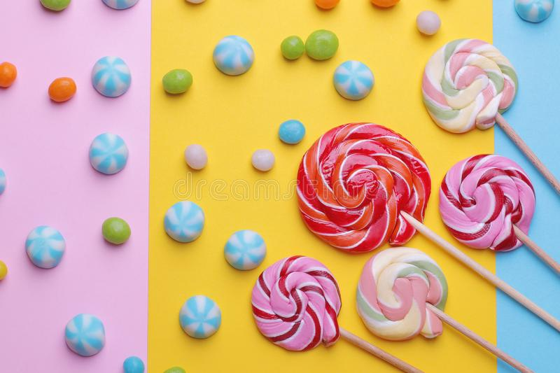 Multicolored round candy and colored lollipops on colored bright backgrounds. stock photo