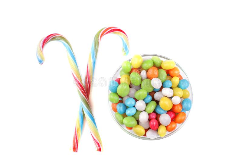 Multicolored round candy in a glass bowl and lollipops on a white background. Isolated. stock images