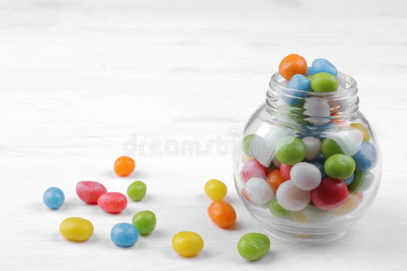 Multicolored round candy in a glass jar on a white background. stock images
