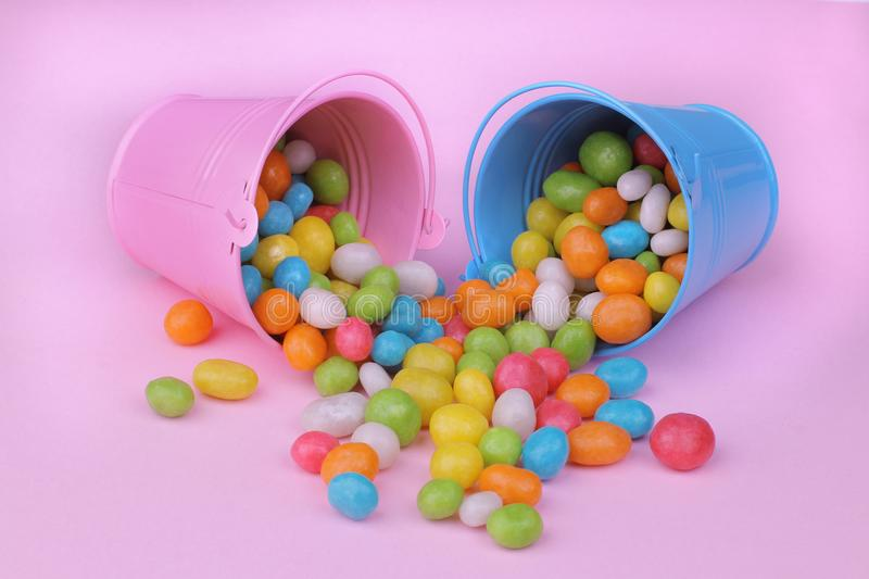 Multicolored round candy in a pink and blue decorative bucket on a pink background. stock images
