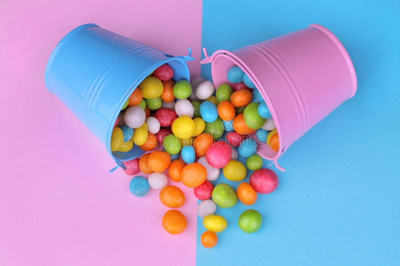 Multicolored round candy in a pink and blue decorative bucket on a pink and blue bright background. stock images