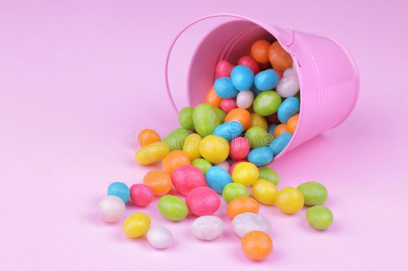 Multicolored round candy in a pink decorative bucket on a pink background. royalty free stock image