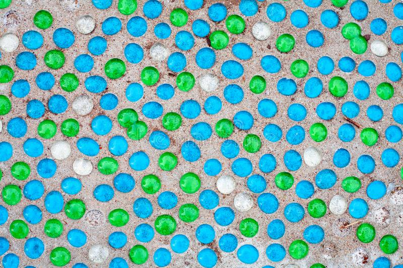 Multicolored round shiny glass stones on a sandy surface stock photo