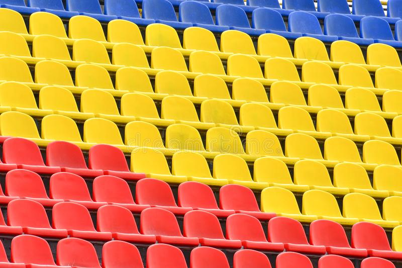 Multicolored rows of seats in a football stadium. Abstract background of empty seats. Arena, audience, chair, public, sport, plastic, seating, horizontal royalty free stock image