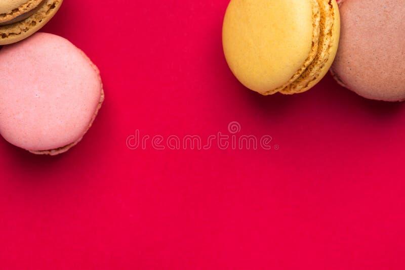 Multicolored Roze Groene Gele Bruine die Mocha-Koffiemakarons op Blauwe Hogere Grens worden verspreid Als achtergrond Het Gebakje stock fotografie