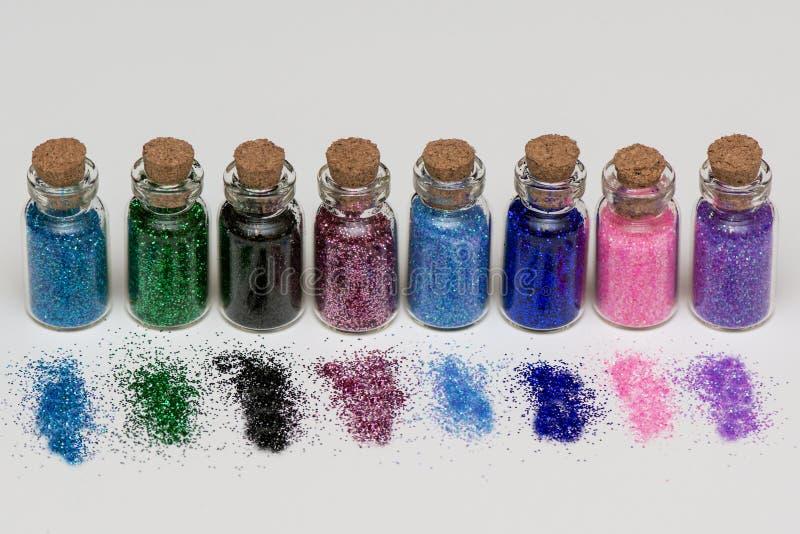 Multicolored schitter voor spijkermanicure en make-up in banken op een witte achtergrond Macro stock fotografie