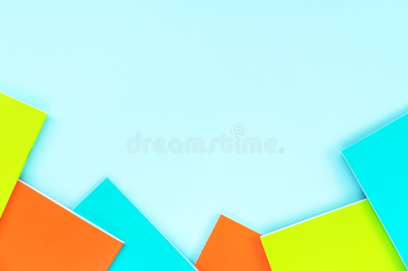 Multicolored school notebooks on a pastel sky blue background stock photo