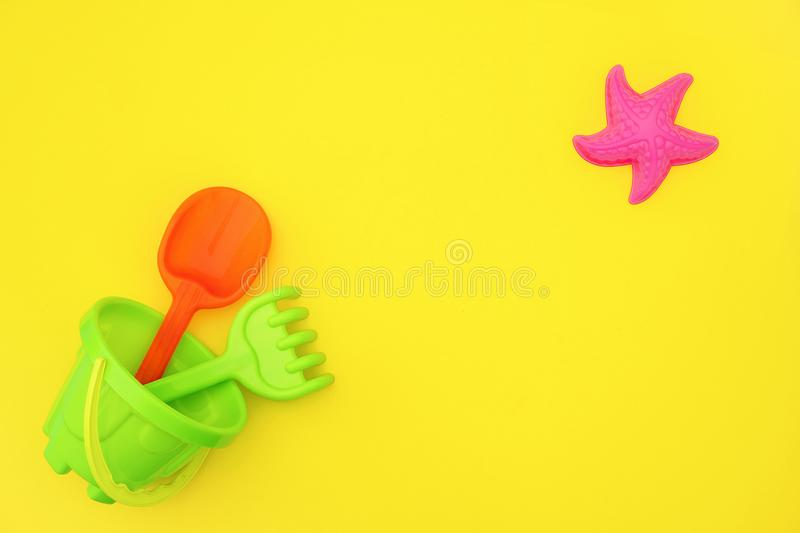 Multicolored set children`s toys for summer games in sandbox or on sandy beach on yellow background with copy space. Top view Fla stock image
