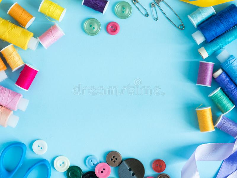Multicolored sewing threads and buttons on blue background with copy space flat lay royalty free stock photo