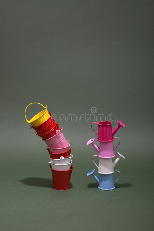 Multicolored small buckets and watering cans. On a green background royalty free stock photo