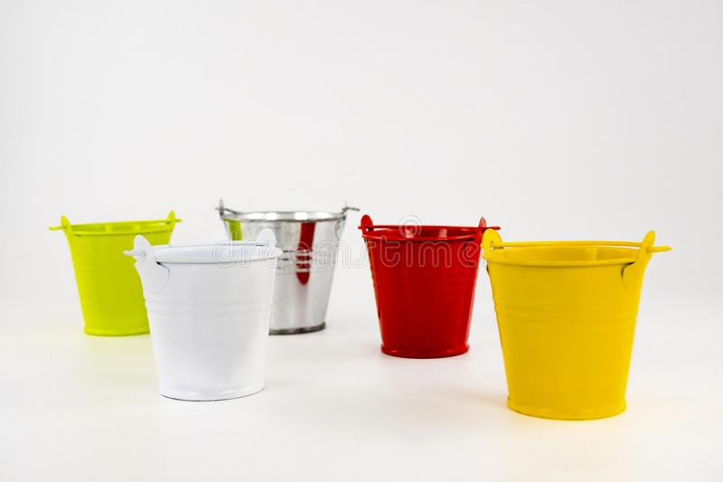 Multicolored small buckets on a white background. Table decorating item stock photography