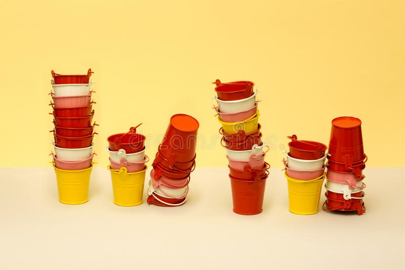 Multicolored small buckets. On a yellow-beige background royalty free stock photography