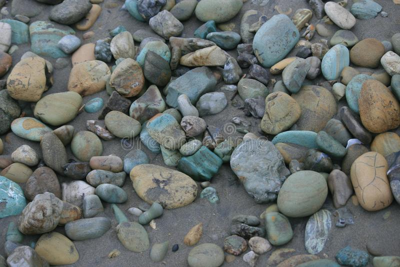 Multicolored smooth stones scattered on the beach stock photo