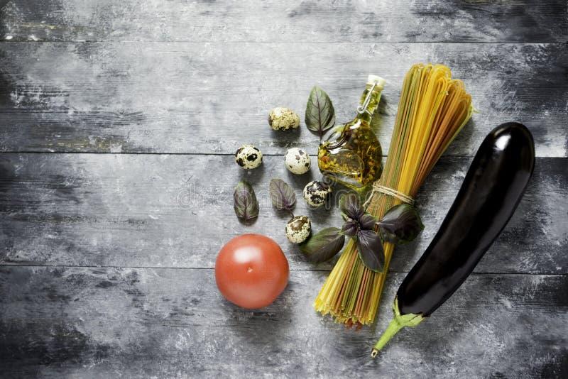 Multicolored spaghetti, groenten, eieren en olijfolie voor het koken van deegwaren stock fotografie