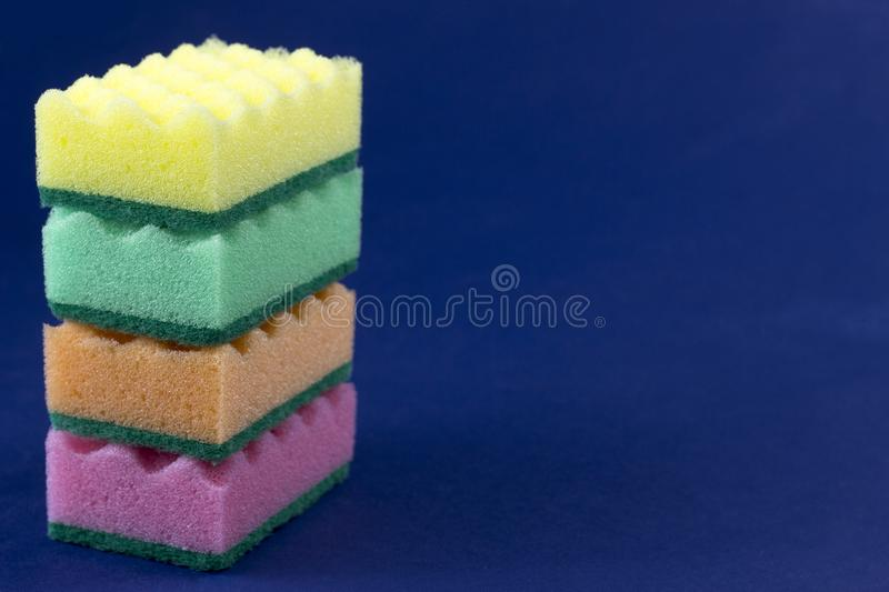 Multicolored sponges for washing on a blue background kitchen stock photos