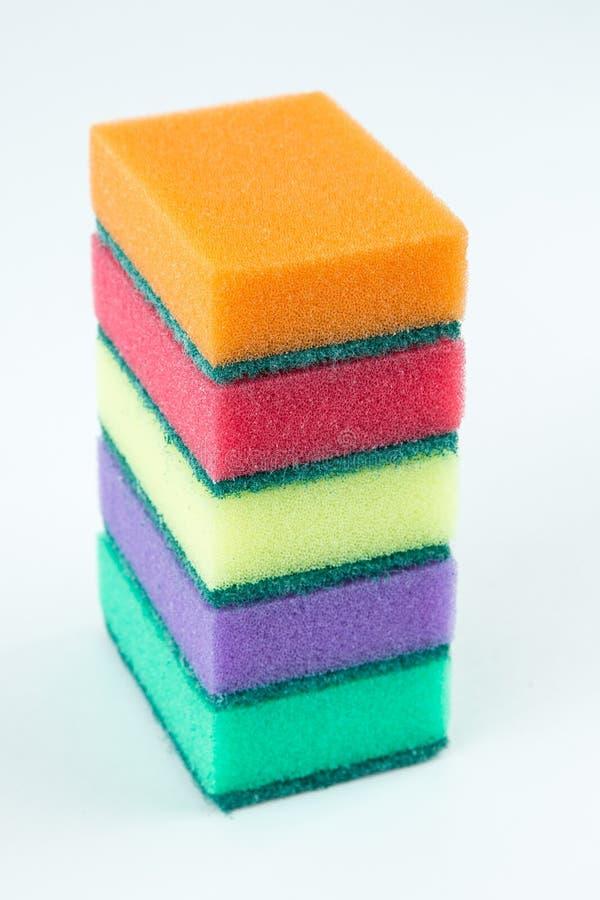 Multicolored sponsen voor wasschotels op wit geïsoleerde achtergrond Selectieve nadruk stock foto