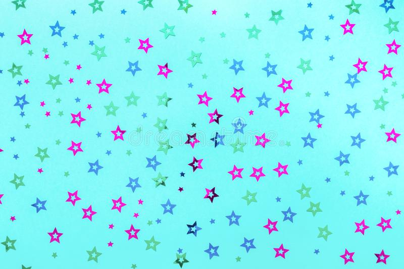 Multicolored stars sprinkles on pastel blue backdrop. Festive holiday background. for your projects. Celebration concept. stock photo