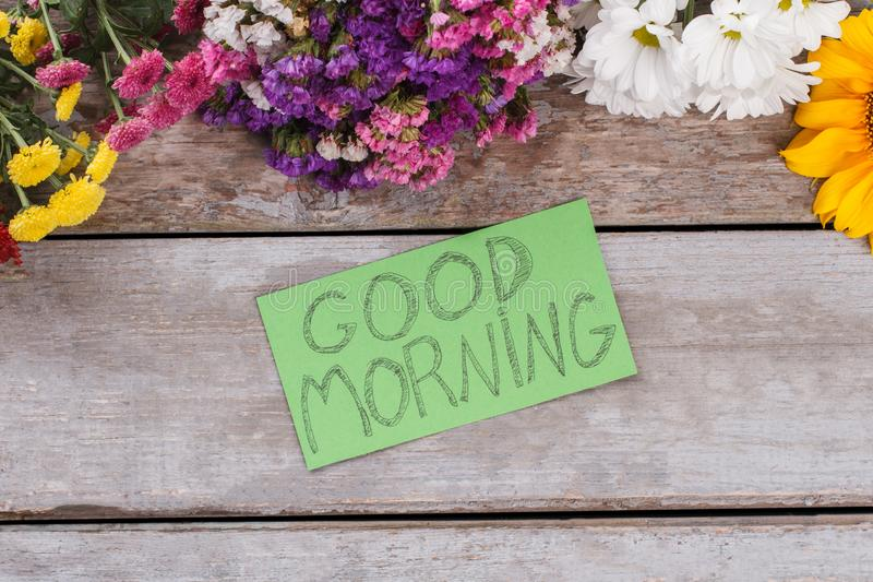 Multicolored statice flowers and good morning wish. Old vintage wooden desk surface background royalty free stock photos