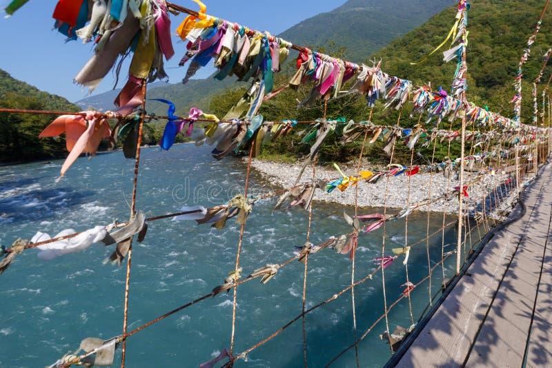 Multicolored stoffenlinten op een voethangbrug over een bergrivier die worden geknoopt royalty-vrije stock foto's
