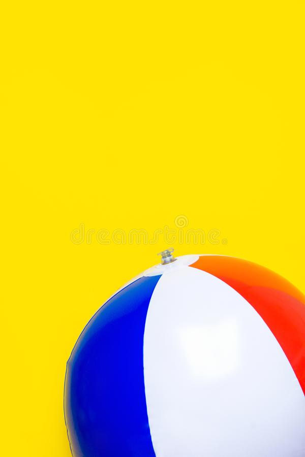 Multicolored striped inflatable beach ball on bright yellow background. Summer sports vacation beach kids fun travel. Concept. Blank placeholder streamer for royalty free stock photography