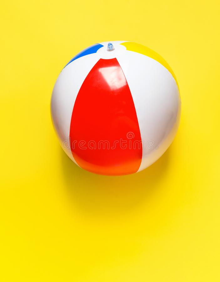 Multicolored striped inflatable beach ball on bright yellow background. Summer sports vacation beach kids fun travel concept. Blank placeholder streamer for stock image