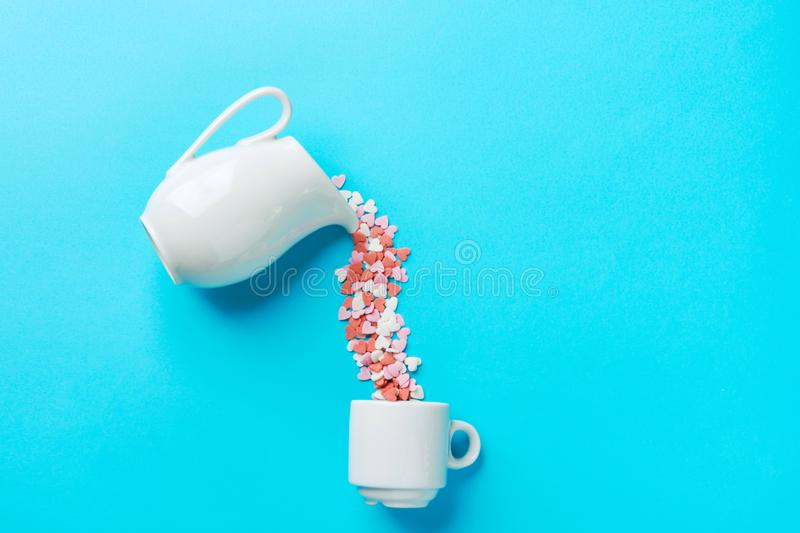 Multicolored sugar candy hearts imitating pouring liquid coffee tee from white milk jug pitcher into cup. Creative food flat lay stock images