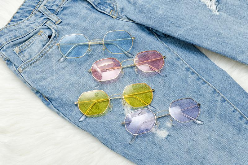 Multicolored sunglasses on jeans. Fashionable concept.  stock image