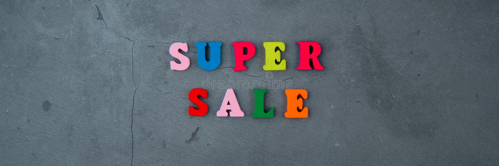 The multicolored super sale word is made of wooden letters on a grey plastered wall background.  stock photography