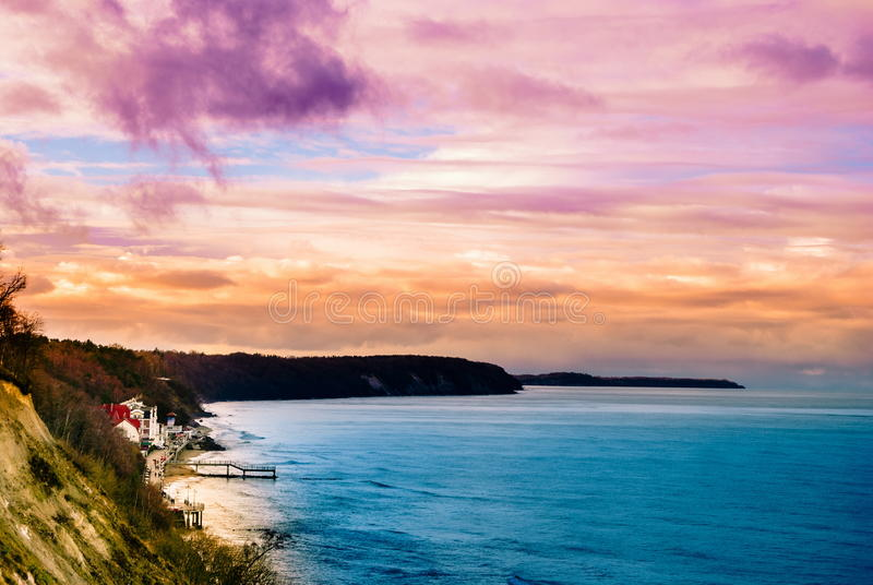 Multicolored surreal sunset view of a rocky coastline. Beautiful landscape photography. Background tecture for travel and adventure stock photo
