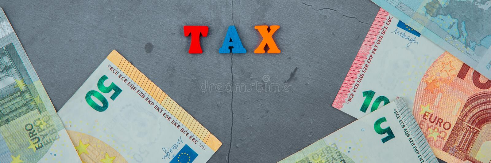 The multicolored tax word is made of wooden letters on a grey plastered wall background.  stock photography