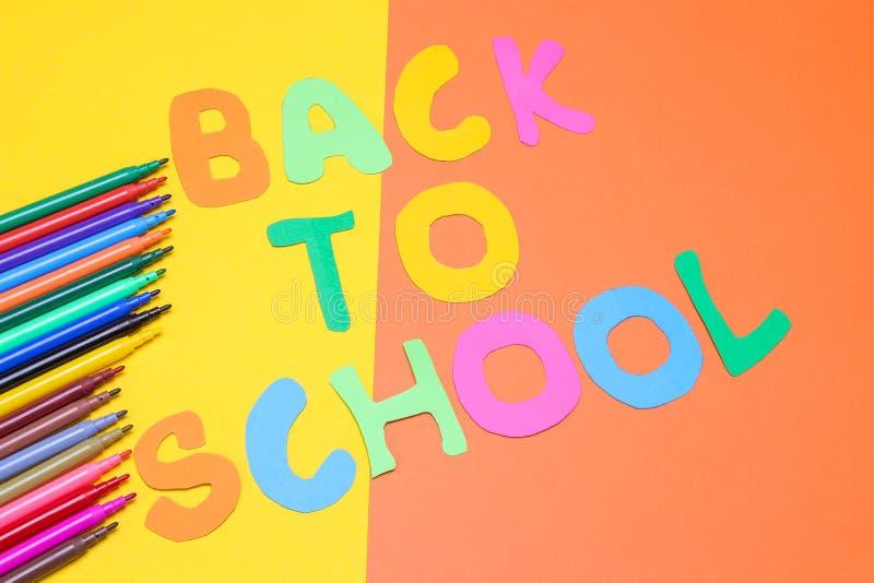 Multicolored tellers en inschrijving terug naar school op een gele en oranje achtergrond stock foto's