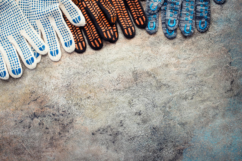 Multicolored textile working gloves on old background. With copy space royalty free stock photography