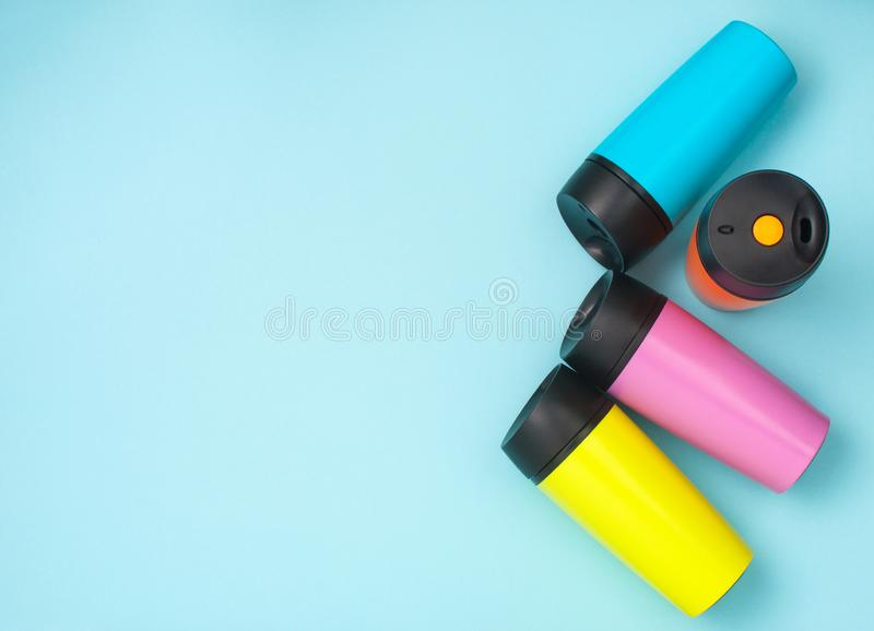 Multicolored thermo mugs on the blue background with copy space stock images