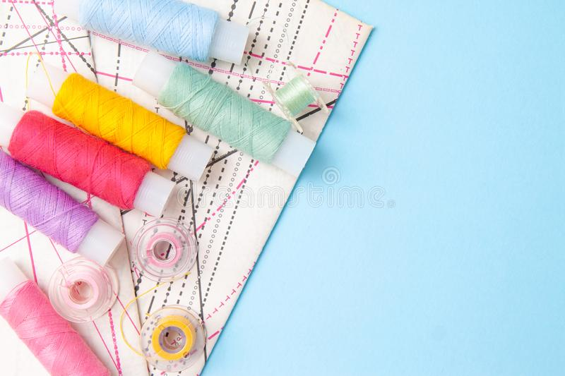 Multicolored thread coils and measuring tape on blue background. Sewing supplies, pattern and accessories for needlework, stock photo