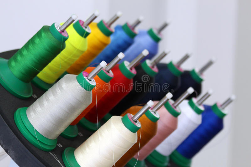Multicolored threads. Closeup of many multicolored threads on reels mounted on a professional machine, ready to embroider and sew