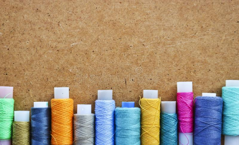 Multicolored threads on a roll for sewing on a blurred wooden background. With copy space royalty free stock image