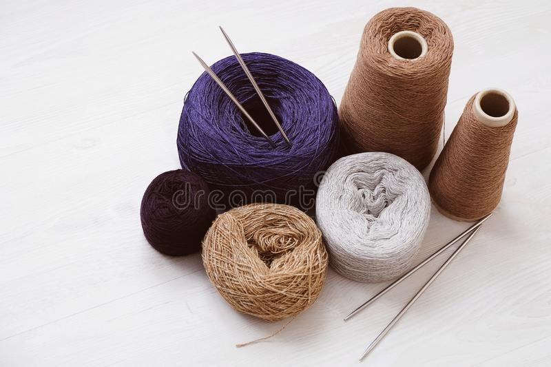 Multicolored threads, skeins and tangles of Italian wool yarn, knitting needles on a white isolated background. stock images