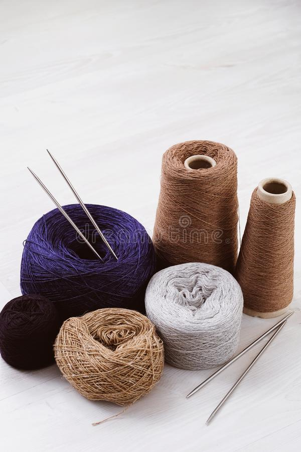 Multicolored threads, skeins and tangles of Italian wool yarn, knitting needles on a white isolated background. The concept of knitting, needlework, handmade stock photo