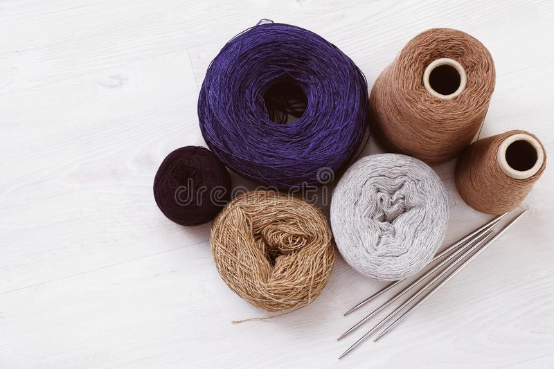 Multicolored threads, skeins and tangles of Italian wool yarn, knitting needles on a white isolated background. The concept of knitting, needlework, handmade stock image